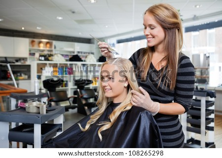 Young woman having her hair dyed by beautician at parlor #108265298