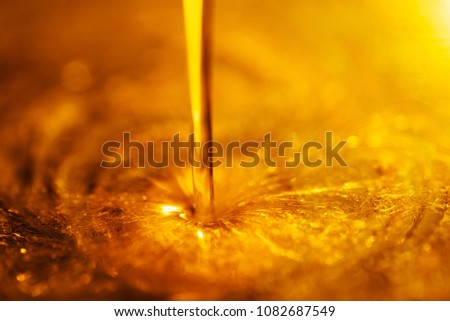 Orange liquid and viscous stream of motorcycle motor oil like a flow of honey close-up. #1082687549