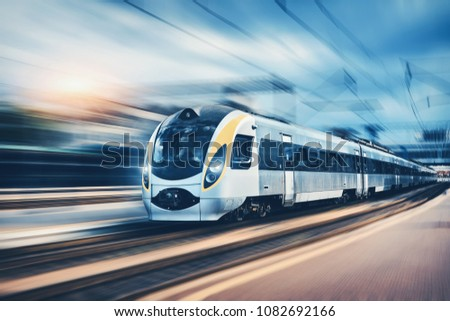 High speed passenger train in motion on the railway station at sunset in Europe. Modern intercity train on railway platform with motion blur effect. Urban scene with railroad. Railway transportation #1082692166