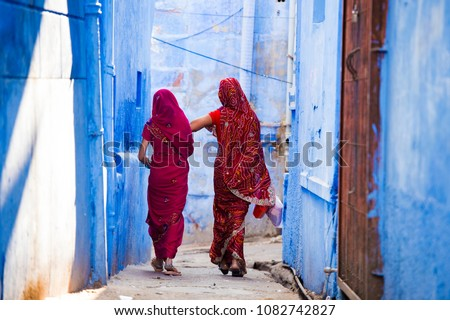 Two women dressed in the traditional Indian Saree are walking through the narrow streets of the blue city of Jodhpur, Rajasthan, India. Royalty-Free Stock Photo #1082742827