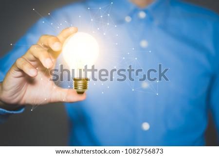 Businessman holding light bulbs, new ideas and Innovative idea concept. #1082756873