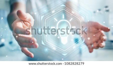 Businessman on blurred background using lightbulb idea interface 3D rendering #1082828279