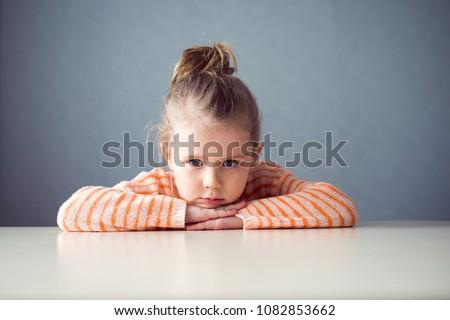 sad girl preschooler at the table #1082853662