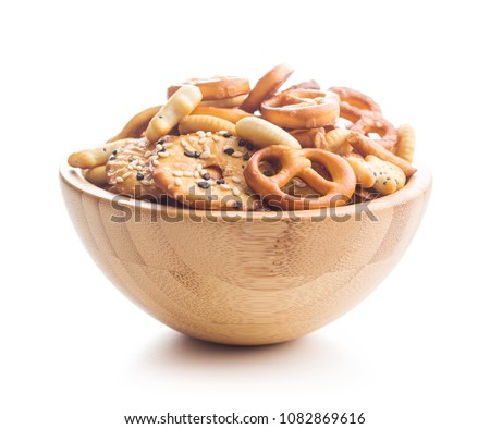 Mixed salty snack crackers and pretzels in bowl isolated on white background. #1082869616