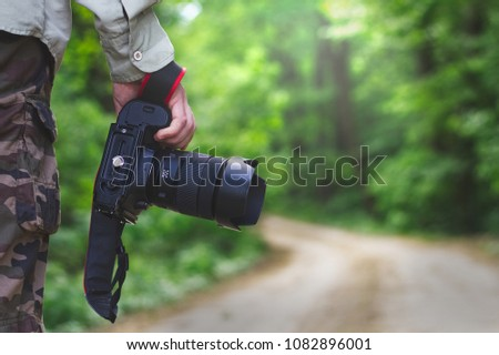 Photographer holding a camera outdoors. Man wearing camouflage shorts taking pictures of nature in forest. #1082896001