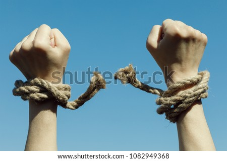 Hands tearing shackles the background of blue sky. Concept of freedom #1082949368