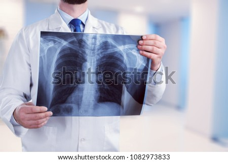 Young male doctor examining x-ray #1082973833