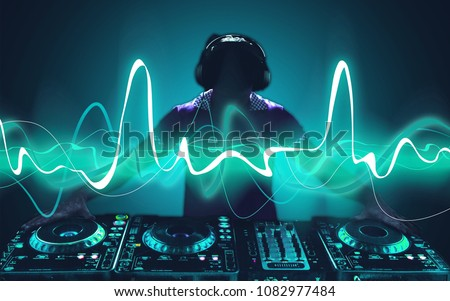 Portrait of confident young DJ with headphones Royalty-Free Stock Photo #1082977484
