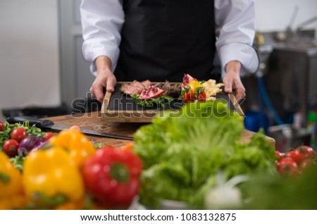 female Chef  in hotel or restaurant kitchen holding grilled beef steak plate with vegetable decoration #1083132875