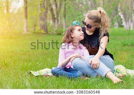 mother and daughter resting on the nature on the green grass, resting, smiling in the summer in Sunny weather, family outdoors in the Park #1083160148