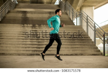 Young man running fast outdoors in the city #1083171578