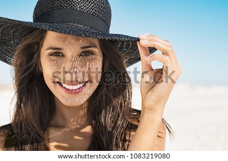 Portrait of beautiful young woman wearing summer black hat with large brim at beach. Closeup face of attractive girl with black straw hat. Happy latin woman smiling and looking at camera at sea. #1083219080