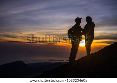 Lombok, Indonesia - April 30, 2017, silhouette couple at mount rinjani. Mount Rinjani (3726m from sea level), is an active volcano in Lombok, Indonesia. #1083234605