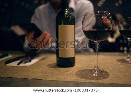 A glass and bottle of red wine on bar desk in front of cheerful handsome young man using his smart phone #1083317375