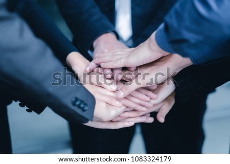 Image of businesspeople hands on top of each other as symbol of their partnership. #1083324179