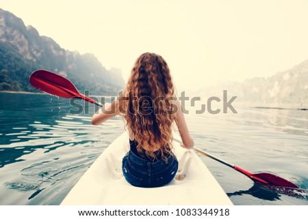 Woman paddling a canoe through a national park #1083344918