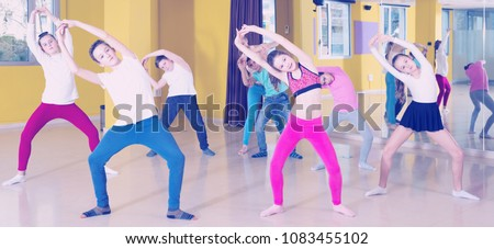 Children dancing synchronous group choreography with female coach in dance hall #1083455102