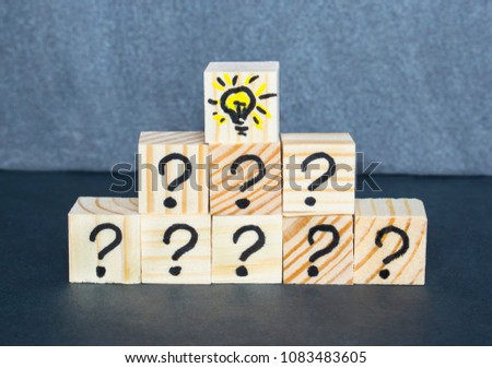Many question marks written on wooden cubes on the dark background.  #1083483605