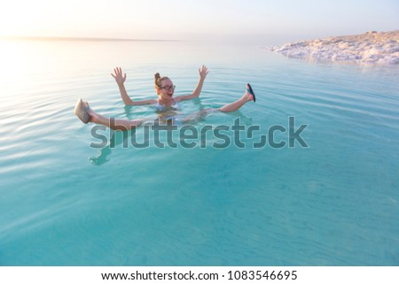 Woman swimming in salty water of a Dead Sea #1083546695