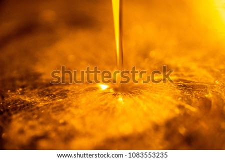 Orange liquid and viscous stream of motorcycle motor oil like a flow of honey close-up. #1083553235