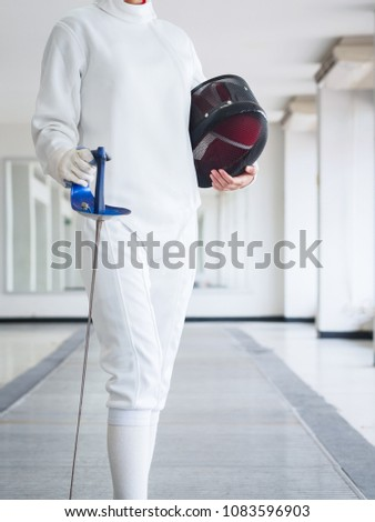Close-up of a fencer in white fencing suit and holding mask and a sword on gym background. sport concept. #1083596903