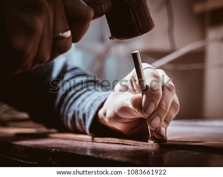 Close up of leather craftsman working with natural leather using hammer. Handbag master at work in local workshop. Handmade concept. Male shoemaker creating product with textile Royalty-Free Stock Photo #1083661922