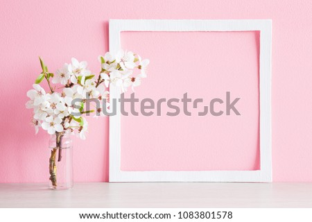 Fresh branches of cherry white blossoms in vase on table. Mockup for special offers as advertising or other ideas. Empty place for inspirational, motivational text or quote at soft pastel pink wall. #1083801578