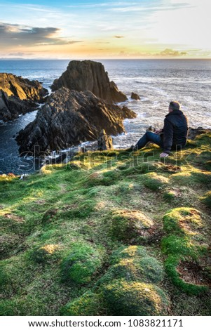 A man sitting on the edge of a sea cliff looking out to the ocean at sunset. This picture was taken at Malin Head Ireland