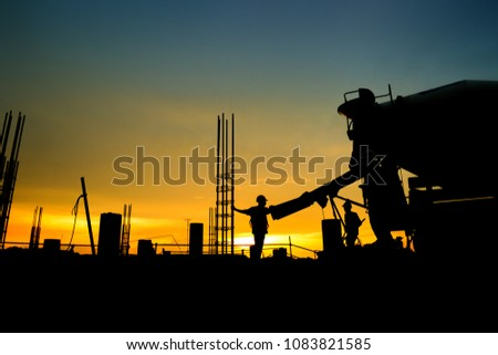 silhouette construction worker Concrete pouring during commercial concreting floors of building in construction site and Civil Engineer inspection work #1083821585