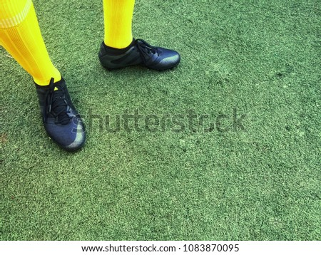 Low section of a football player standing on grass #1083870095