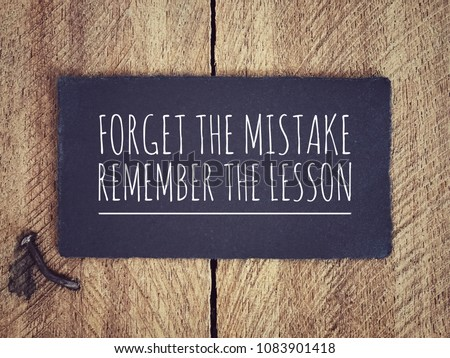 Motivational and inspirational quote - 'Forget the mistake, remember the lesson' written on a black piece of paper with background of wooden wall. #1083901418