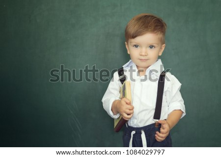 Cheerful smiling boy with books on a green chalkboard background.