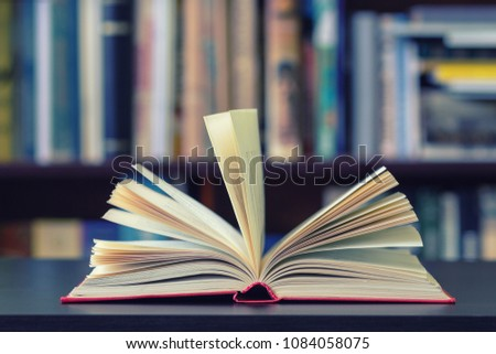 An open book on the background of bookshelves. #1084058075