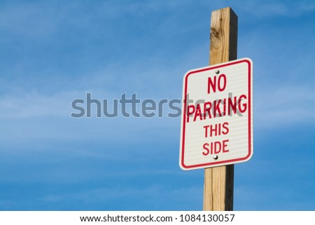 """""""No Parking This Side"""" road sign with vibrant blue skies and clouds in background."""