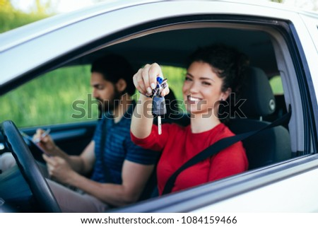 Driving school. Beautiful young woman successfully passed driving school test. She looking sitting in car, looking at camera and holding car keys in hand. #1084159466