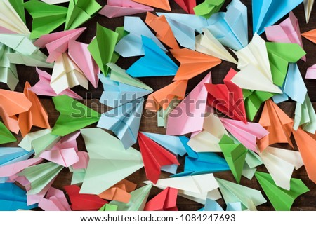 colorful paper airplanes on wooden table background. childhood,freedom,origami and diversity concept #1084247693
