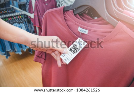 Woman's hand with a cloth hang tag label with QR code in a clothing shop lighting effect. #1084261526