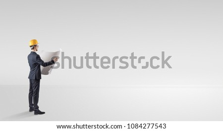 Young architect with construction helmet standing in an empty space and holding a plan #1084277543