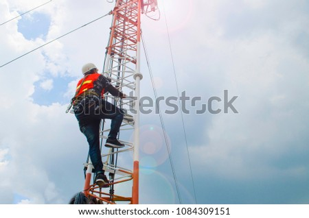 man working on high tower,risk work,man climb telecommunication tower,working with safety equipment. #1084309151