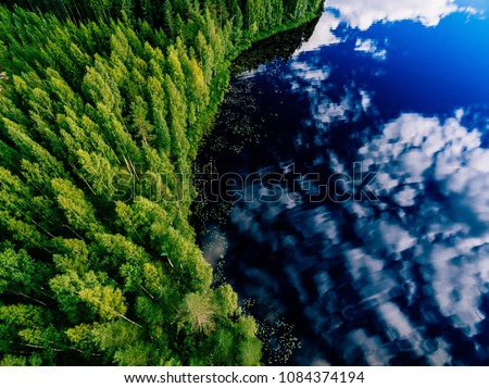 Aerial view of blue lake and green forests on a sunny summer day in Finland. Drone photography #1084374194