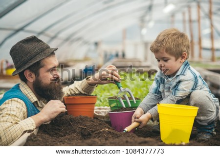 Side view daddy looking at his lovely boy playing with soil. Hipster with stylish beard in fedora hat helping his son. Family spending time out of town. #1084377773