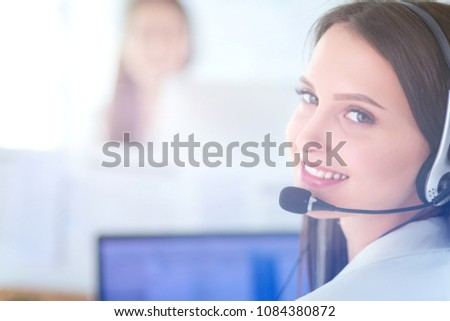 Smiling businesswoman or helpline operator with headset and computer at office #1084380872