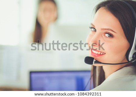 Smiling businesswoman or helpline operator with headset and computer at office #1084392311