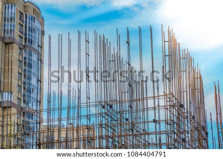 Building construction site with tower crane against blue sky #1084404791