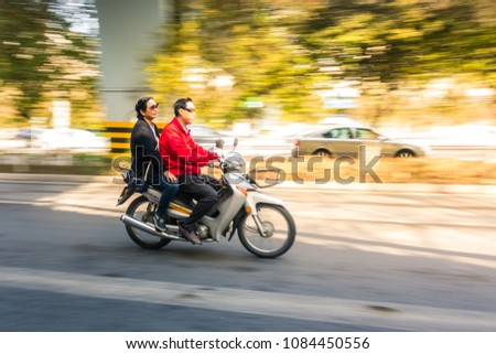 XI'AN, CHINA - MARCH 28, 2018:  A snapshot captures a man riding his motorcycle with his wife down a city street #1084450556