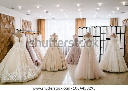 Beautiful wedding dresses, bridal dress hanging on hangers and mannequins in studio, shop. Fashion look. Interior of bridal salon. Wedding show room trendy, modern. #1084453295