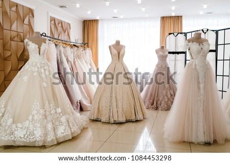 Beautiful wedding dresses, bridal dress hanging on hangers and mannequin in studio. Fashion look. Interior of bridal salon. #1084453298