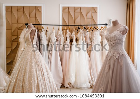 Assortment of dresses hanging on a hanger on the background studio. Fashion wedding trends. Interior of wedding shop. #1084453301