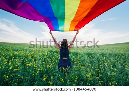 Woman holding the Gay Rainbow Flag on a green meadow outdoors. Happiness, freedom and love concept for same sex couples.  #1084454090
