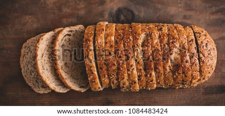 Top view of sliced wholegrain bread on dark ructic wooden  background closeup Royalty-Free Stock Photo #1084483424